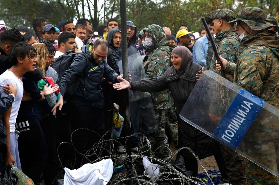 Una dona siriana implora a un soldat macedoni que permeti creuar a membres de la seva família. Yannis Behrakis / Reuters america.aljazeera.com